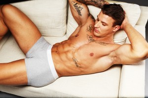Man with beautiful muscular tattooed torso in underwear lying on